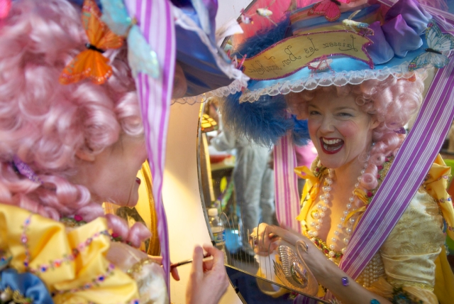 Woman dressed as Marie Antoinette laughs while looking into a mirror on Mardi Gras day.