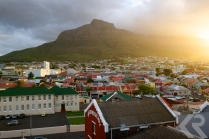 Dramatic view from the top of the Old Biscuit Mill of the surrounding neighborhood of Woodstock and the mountains of Cape Town at sunset.