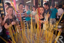American students placing incense into urn in Vietnam.