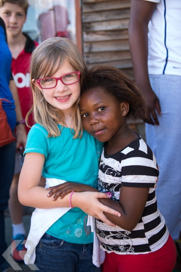 Young white girl hugging a young black girl in South Africa.