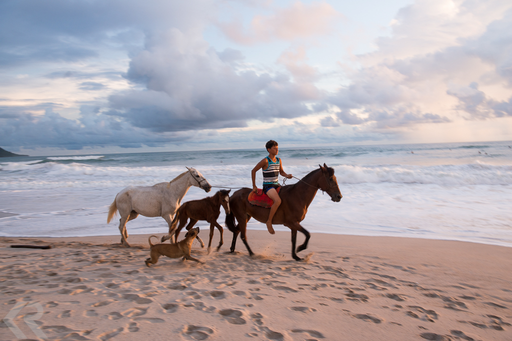 Man riding horses on Costa Rican beach.