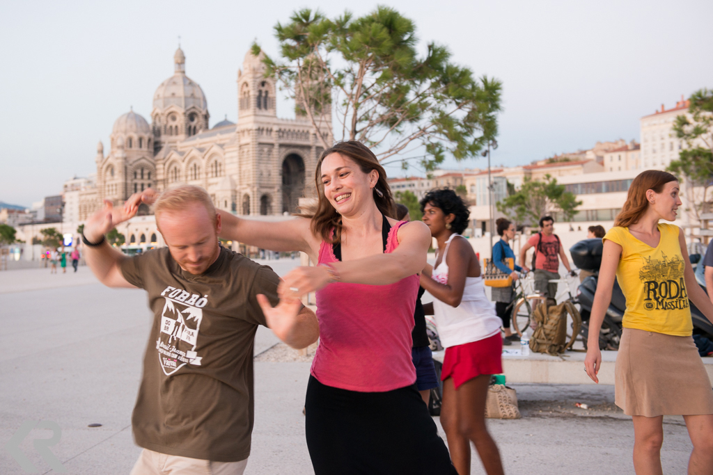 People dancing in front of the Marseille Cathedral at sunset.