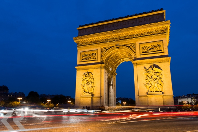 The Arc de Triomphe at dusk in the Place Charles de Gaulle in Paris, France.