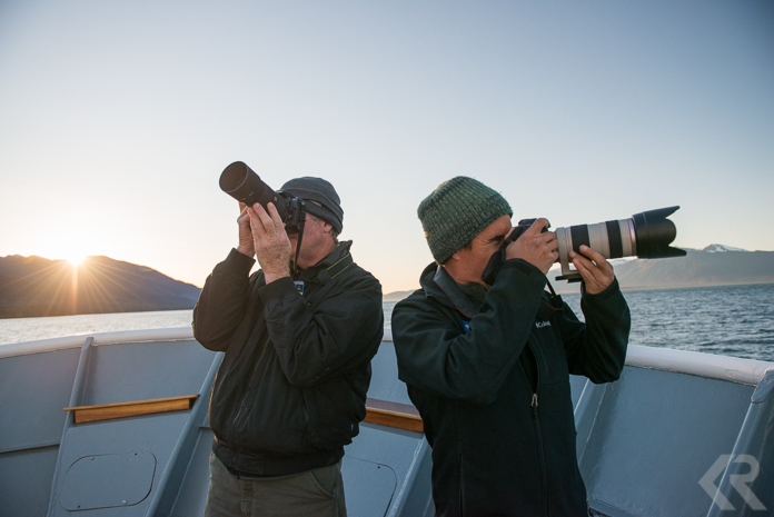 Two photographers on the bow of a ship.