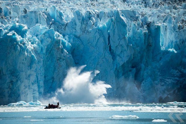 A glacier calves in front of a zodiac filled with people.
