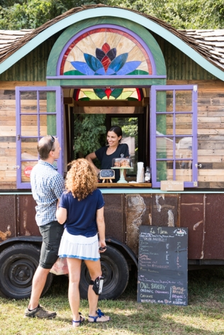 Chantal Bérot, the owner of Le Bon Cafe, chats with customers from her mobile coffee shop at the River Arts District Farmers Market.